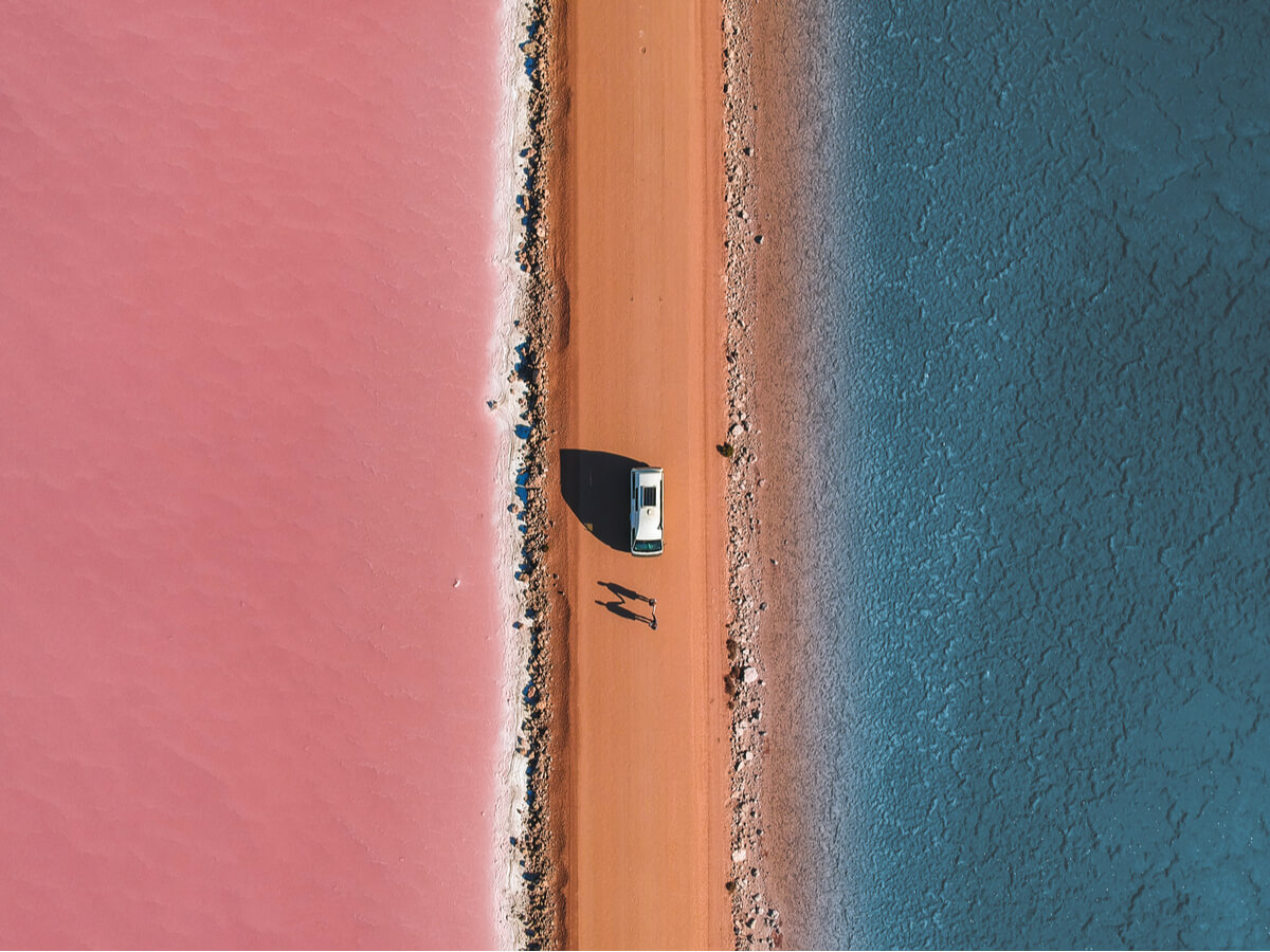 A campervan travelling Australia parked by a salt lake in the Macdonnell Ranges