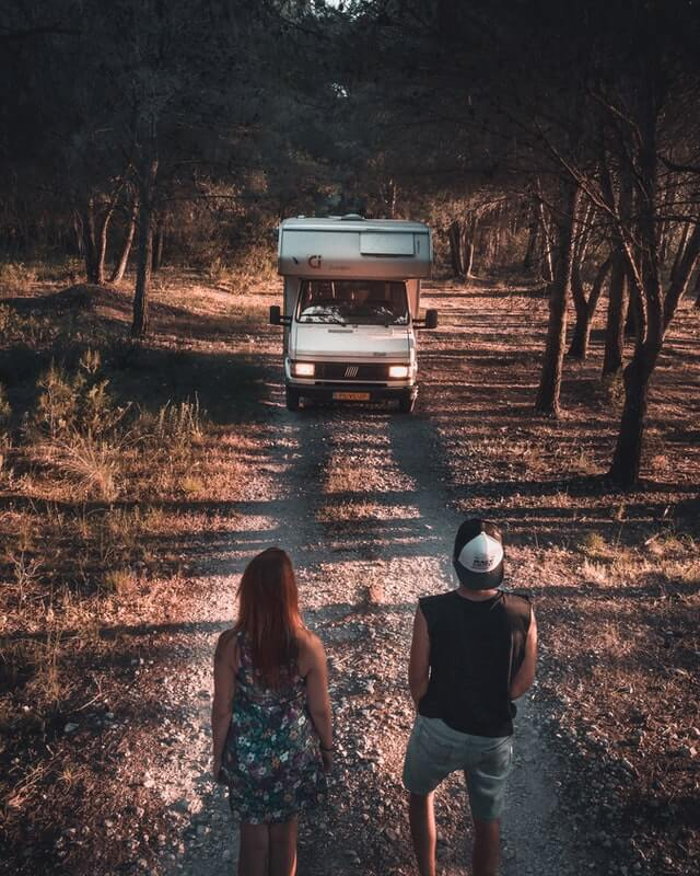 A couple living in a van staring at their motorhome on an empty dirt road