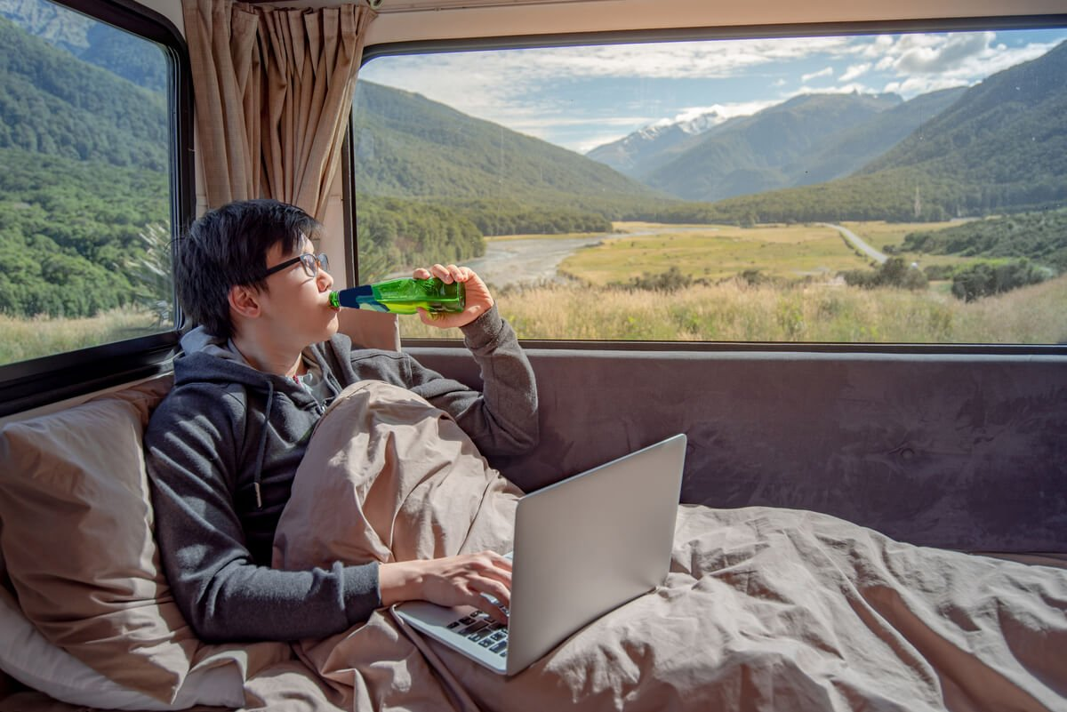 A man working as a digital nomad while living in a van