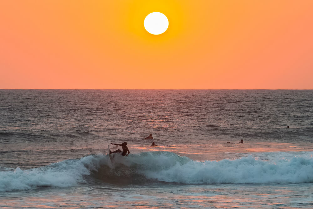 Surfing below a Hikkaduwa sunset