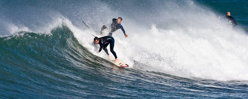 Surfer snakes another's wave