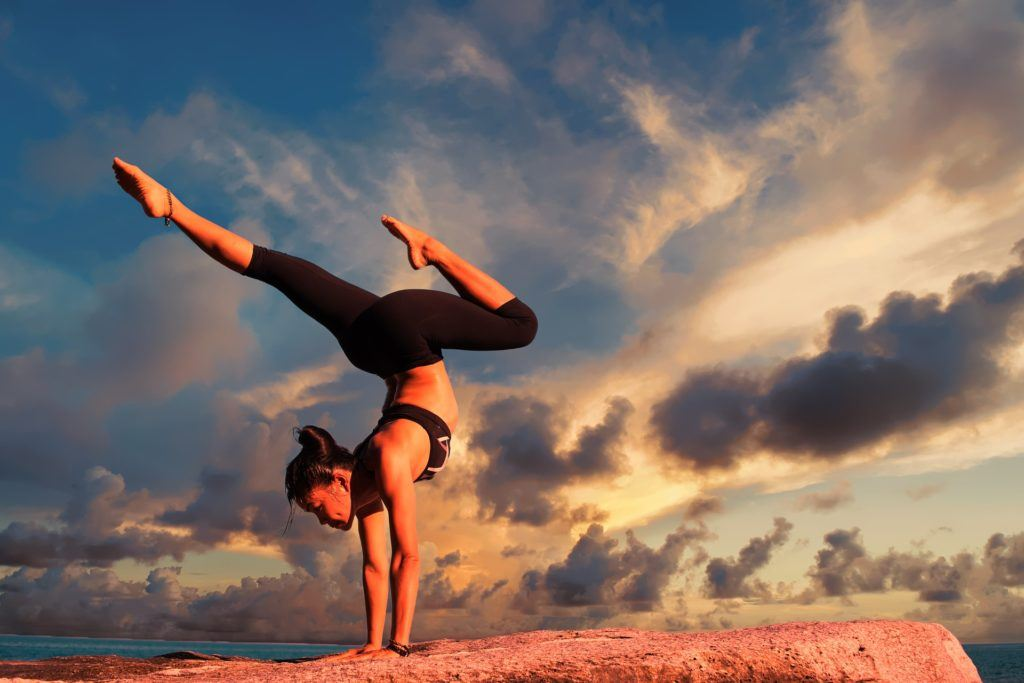 A woman backpacking cambodia practises yoga handstands at the beach