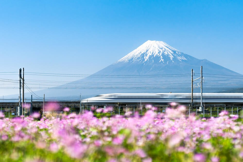 A Japan bullet train traveling safe with Mount Fuji behind