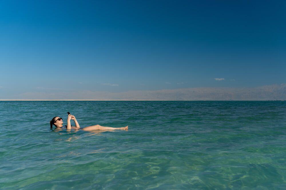 Woman enjoying her mobile internet in Israel in the Dead Sea
