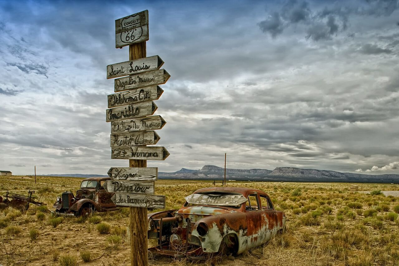 route 66 sign with rusted cars - the quintessential american road trip