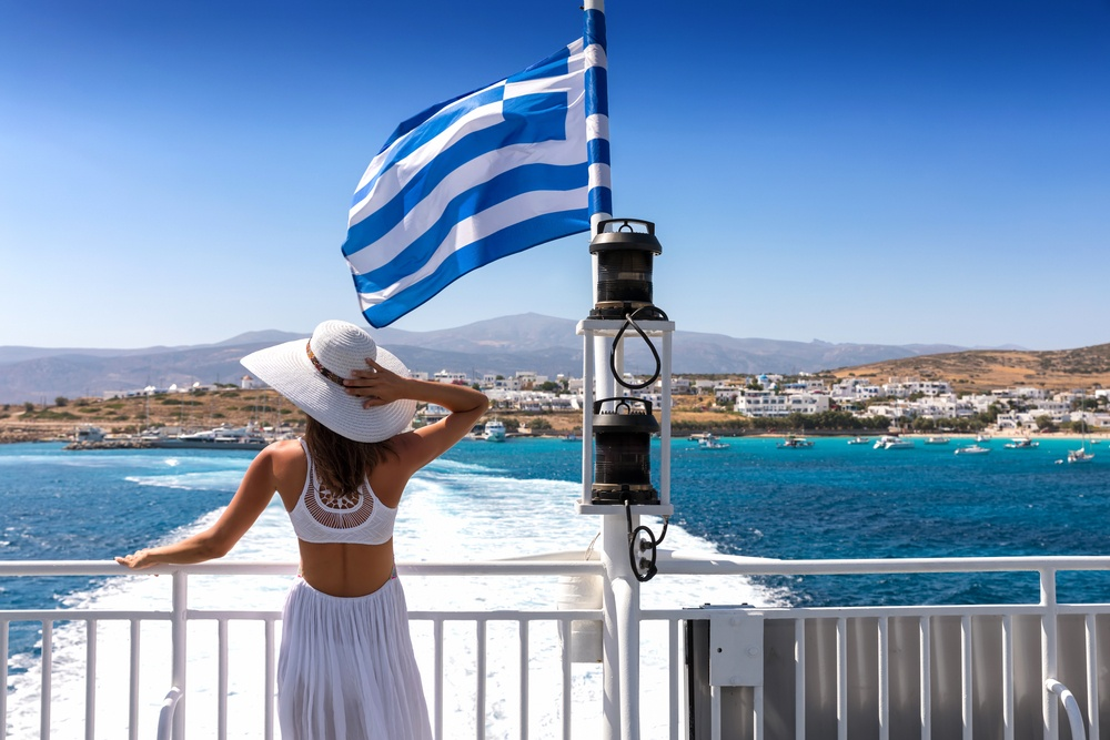 A female tourist in Greece catches a public ferry with the Greek flag