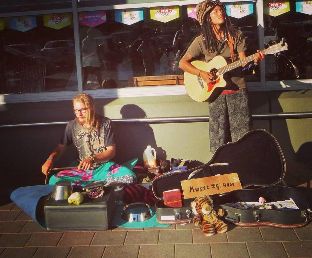 Two travellers busking, one with his portable guitar