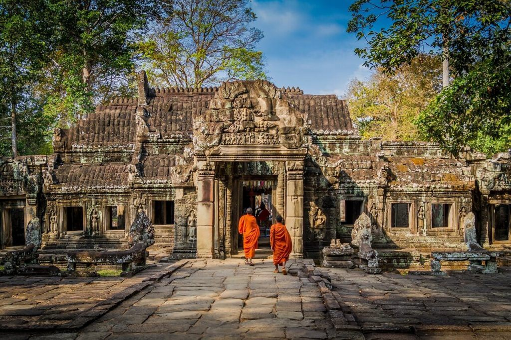 Two monks visiting an ancient temple site in Cambodia