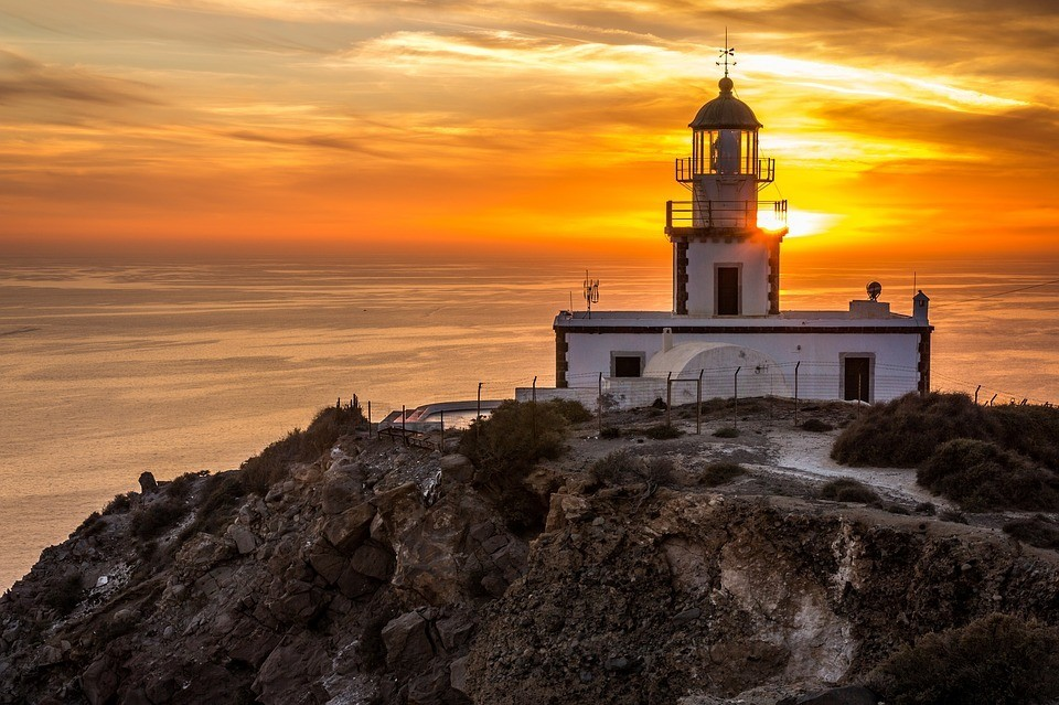 Lightouse and sunset - popular tourist attraction in Santorini, Greece