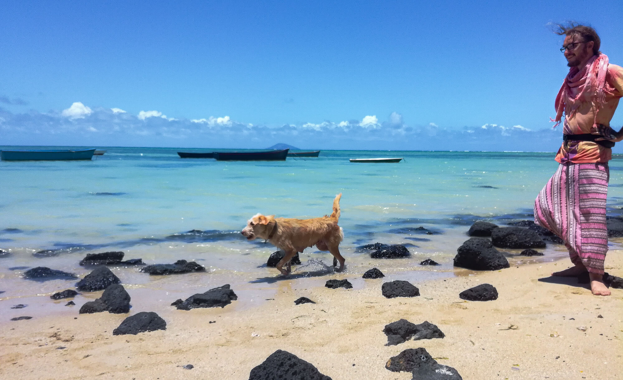 A man and a dog on a beautiful public beach in Mauritius