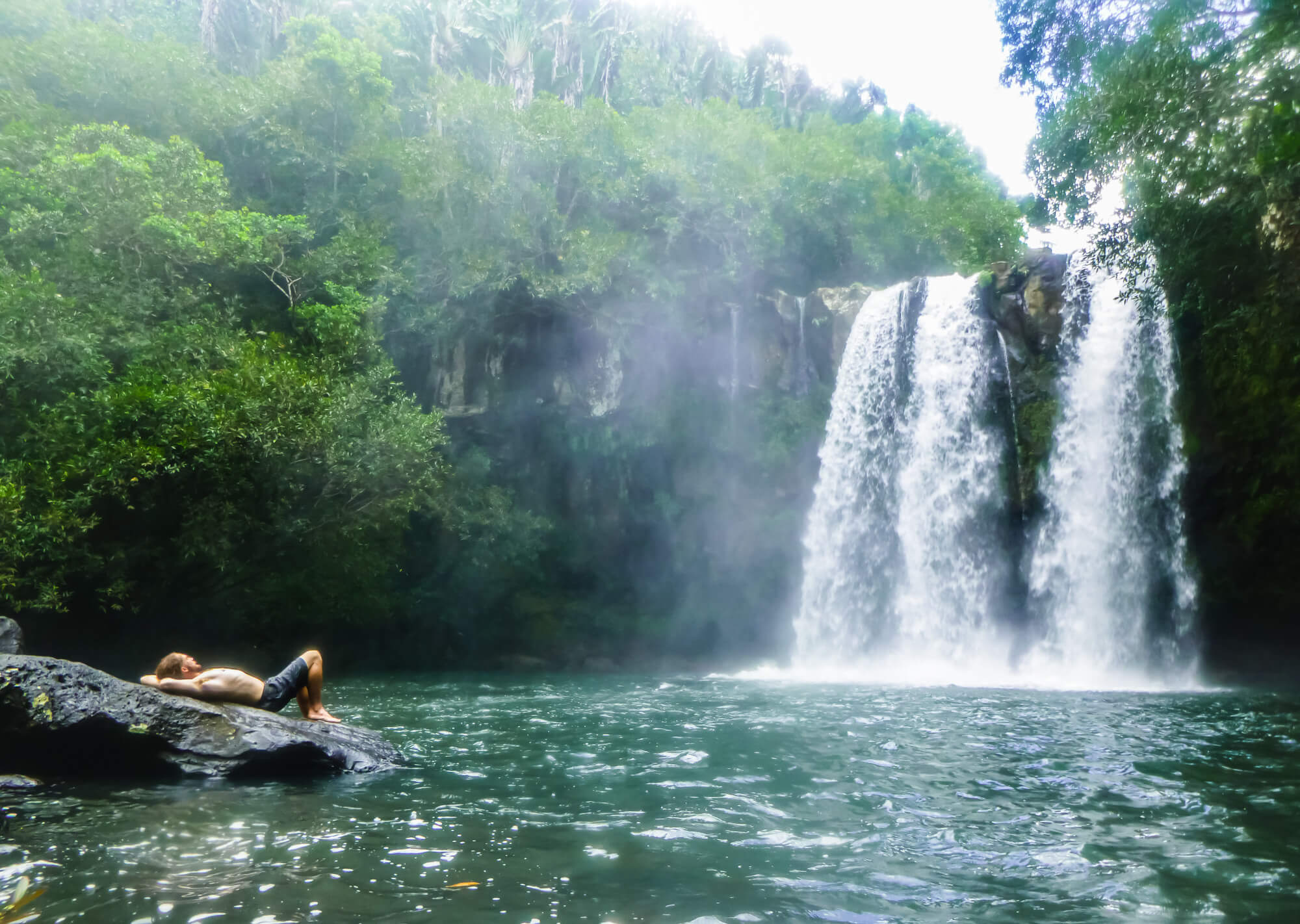 Man takes a break from his diving trip in Mauritius at a waterfall
