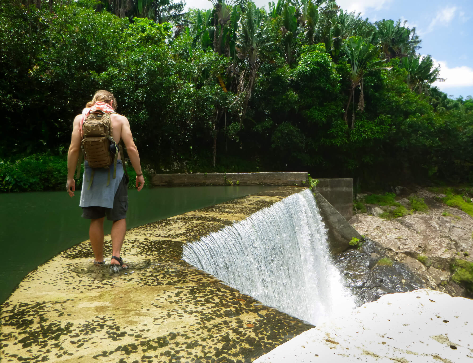 Man hiking across a waterfall while on a cheap holiday in Mauritius