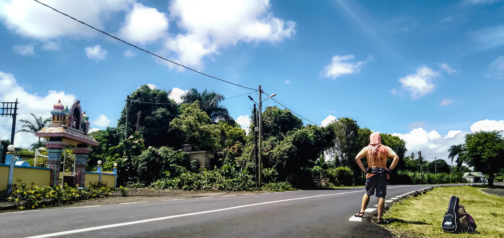 A backpacker hitchhiking in Mauritius to save on travel cost