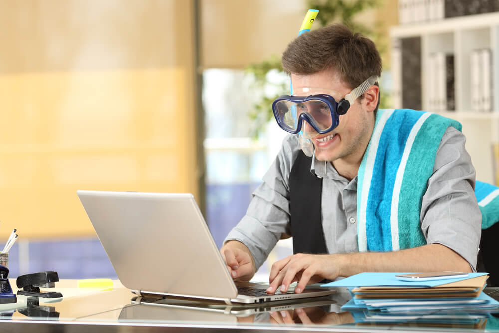 Businessman with safety goggles at a laptop extending his visa for Mauritius