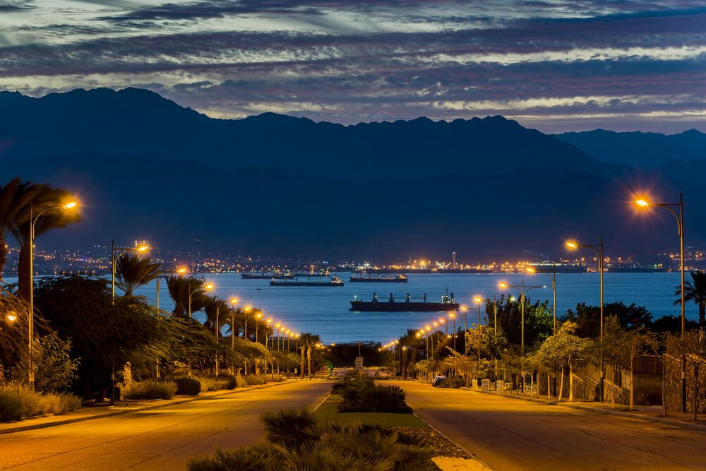 Eilat city and main street at dawn with the Red Sea and Jordanian mountains behind