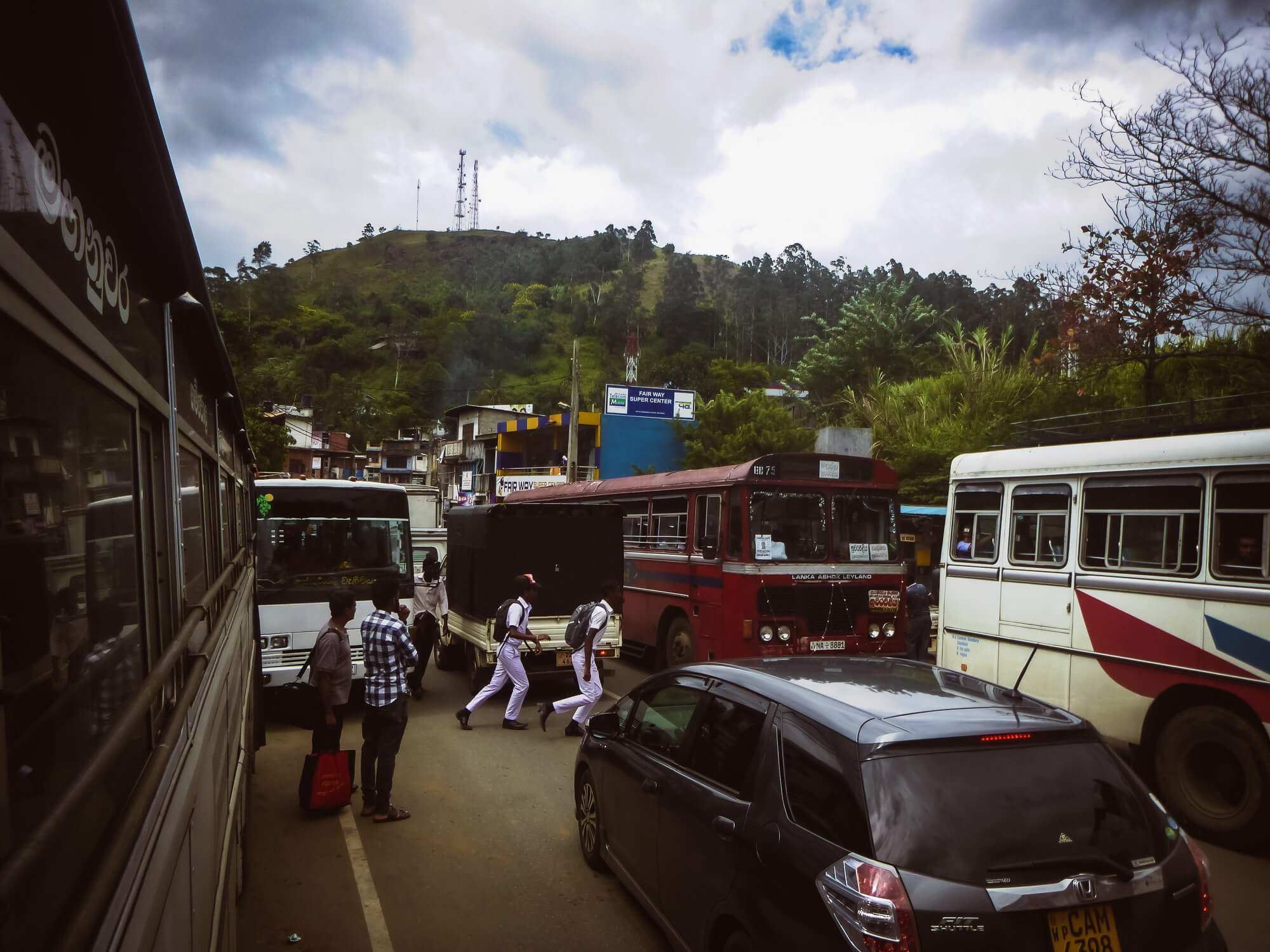 Several public transport buses in Sri Lanka on a busy city road