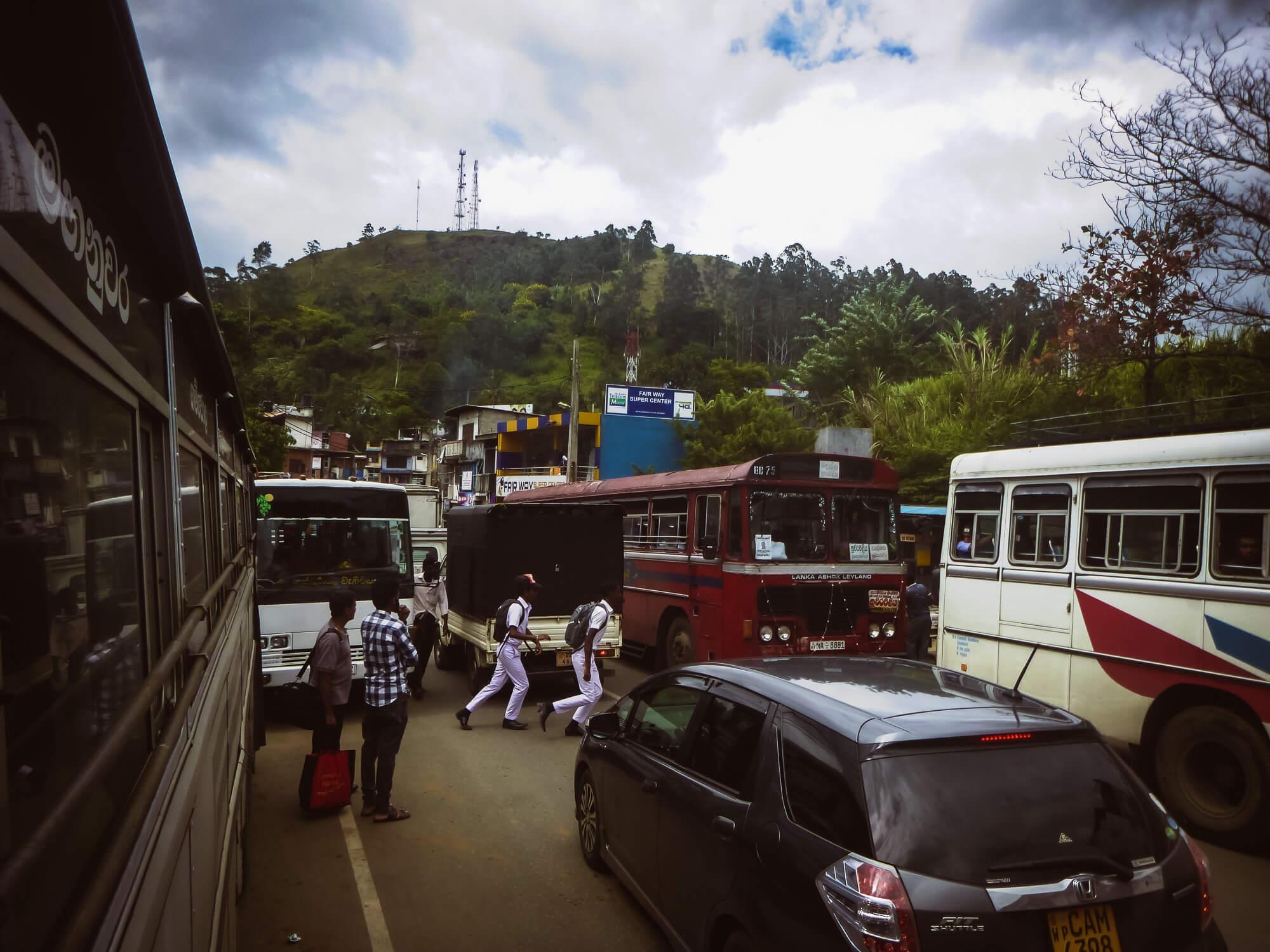 Two boyes in Sri Lanka cross a busy street full of buses