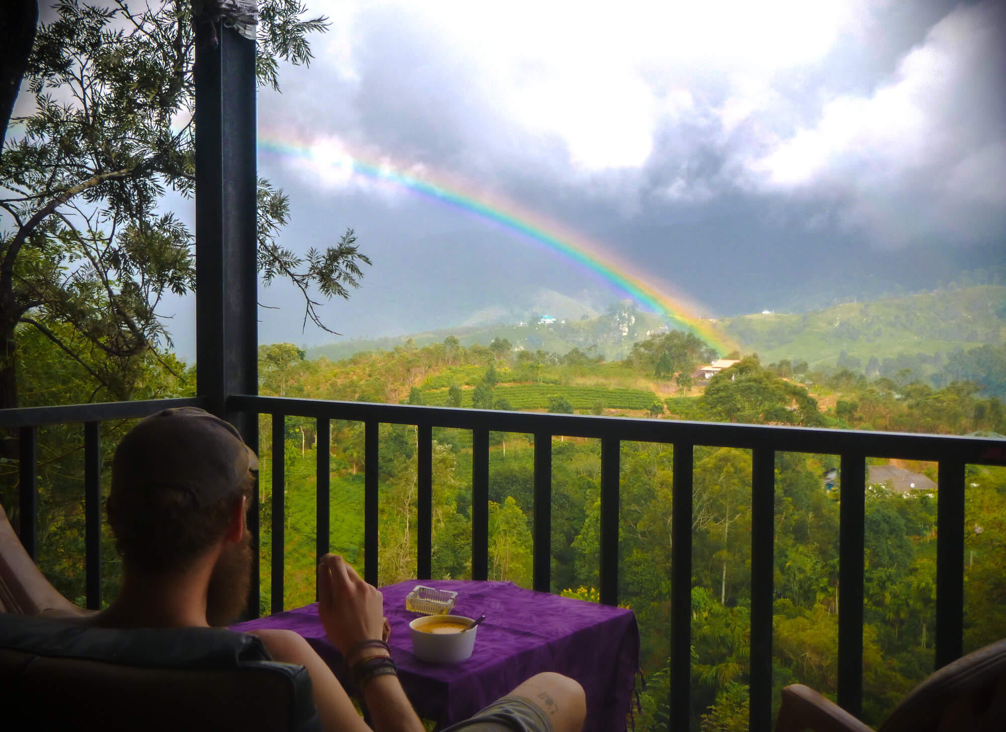 The owner of a sustainable hostel in Sri Lanka enjoys a rainbow over breakfast