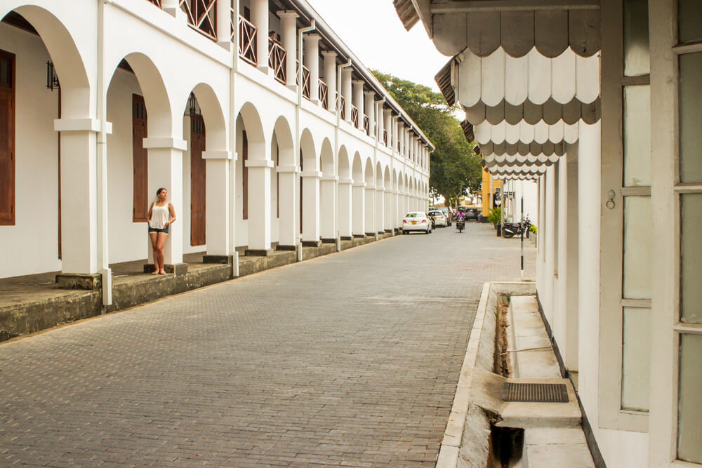 Backpacker in the tourist destination  Galle Fort poses against a white building