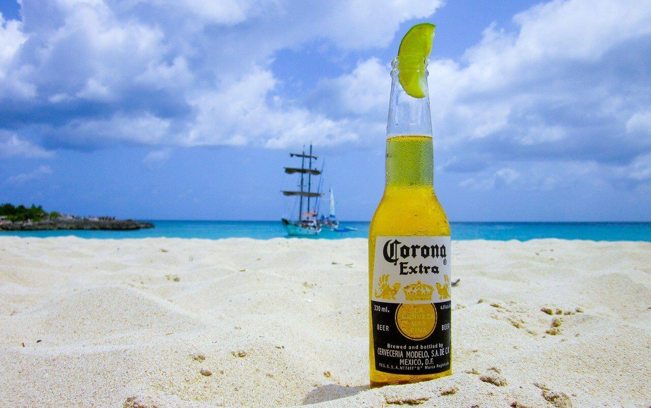 A corona beer and lime on the beach of a country reopened to tourism after COVID lockdowns