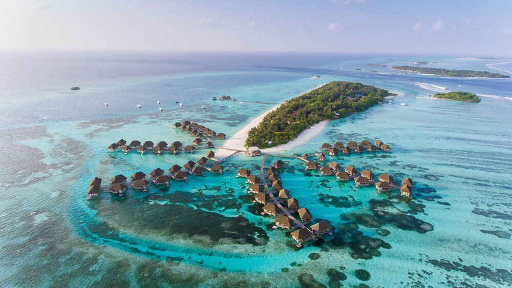 An atoll surrounded by over-water bunglaow accommodation in the Maldives