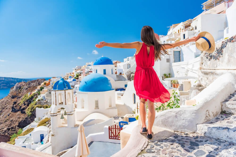 A tourist in Oia celebrates her travels in Greece