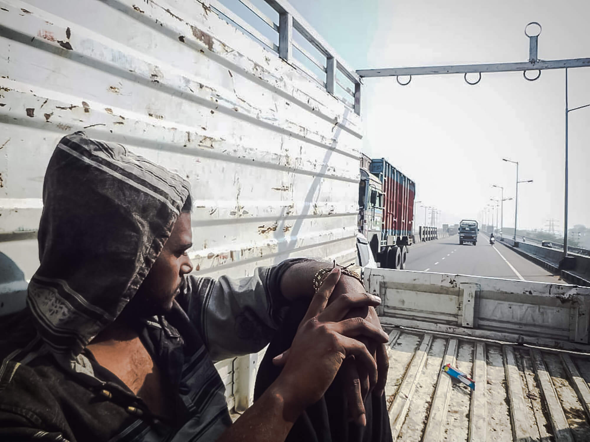 A man rides in a truck after finding a travel partner to hitchhike India with
