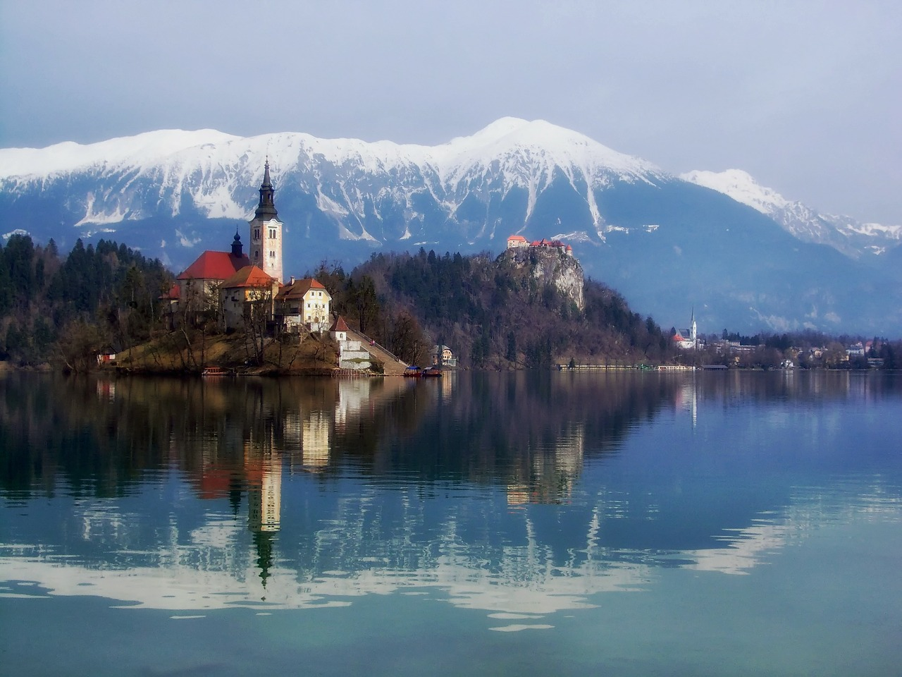 Snow capped mountains rise above a cathedral and some water in the Balkans.