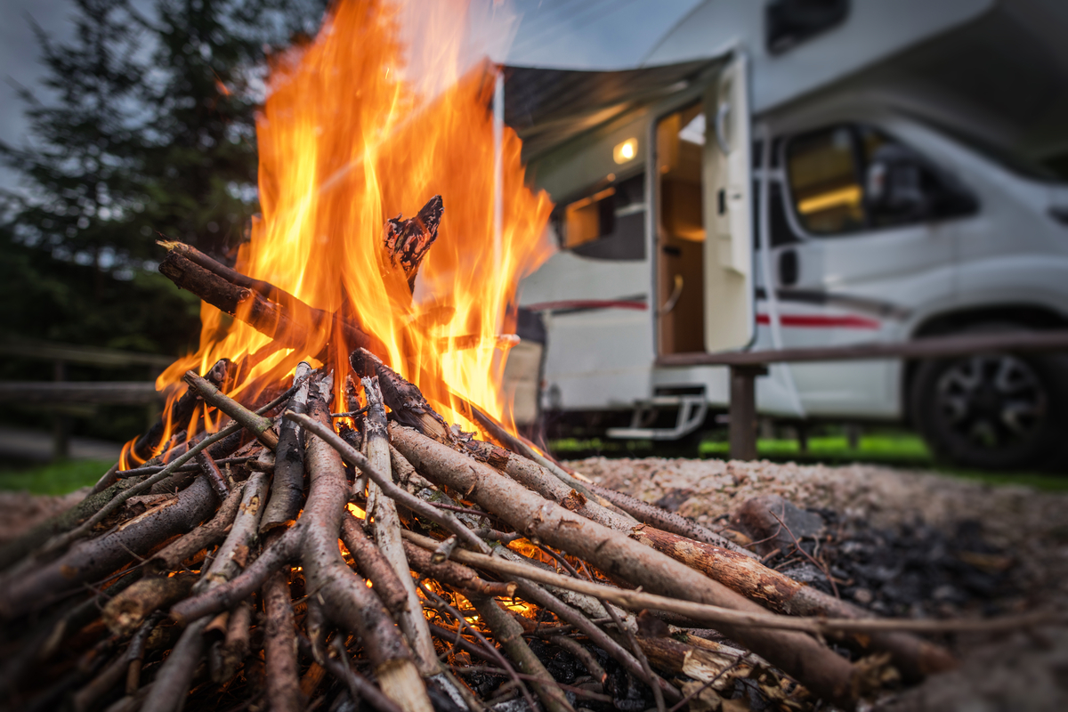 A campfire in front of a parked motorhome in an RV campground