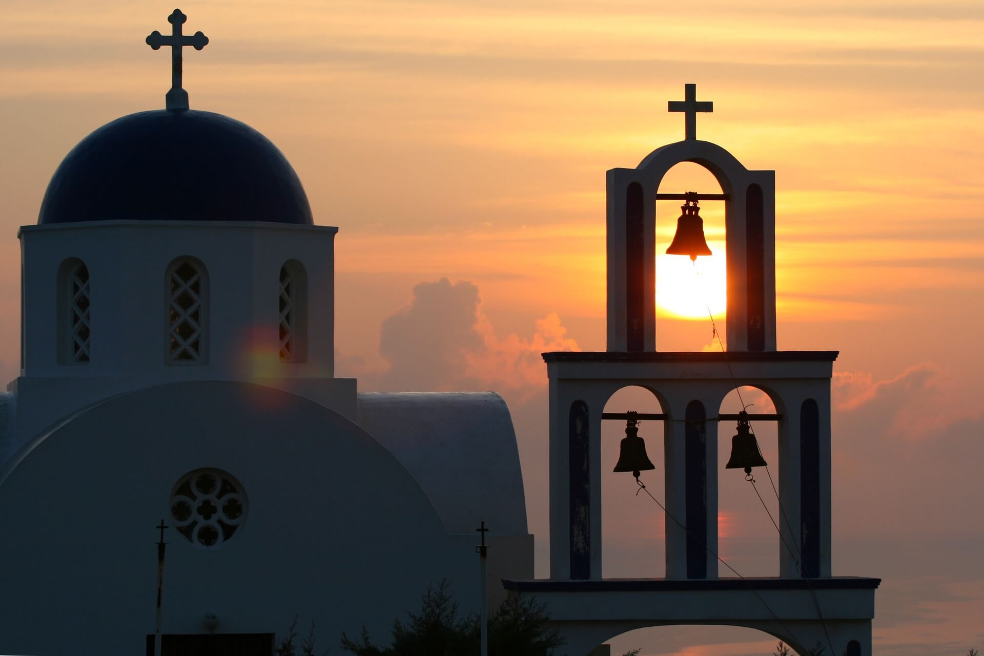 An sunset behind a church in Oia, Santorini