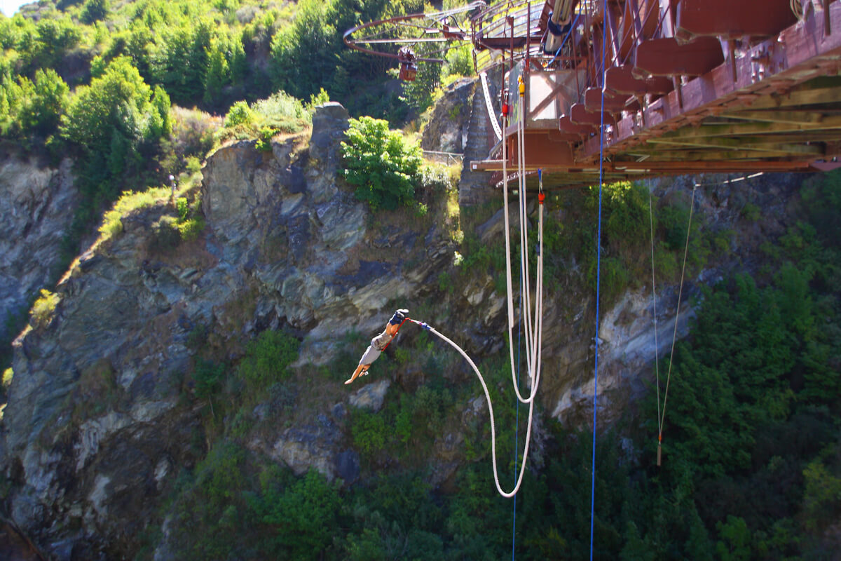 A backpacker in Queenstown does a bungy jump from Kawarau Bridge