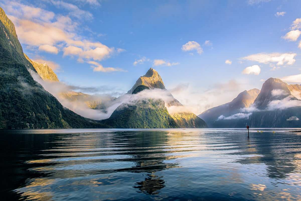 Misty mountains over still black water at Milford Sound, Fiordlands - top destination in New Zealand