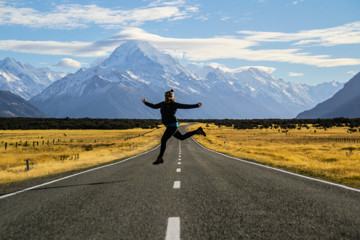 Woman jumps for joy on the road driving to Mount Cook in South Island