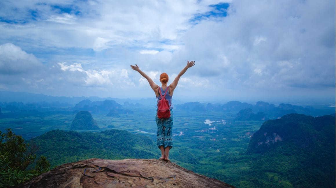 A digital nomad in Thailand celebrates at a lookout after a hike