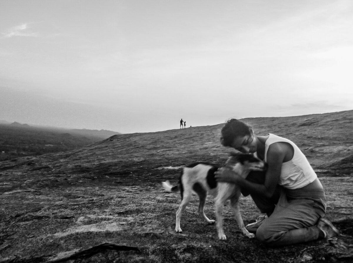 A kind backpacker travelling Sri Lanka cuddles a dog at Sigiriya