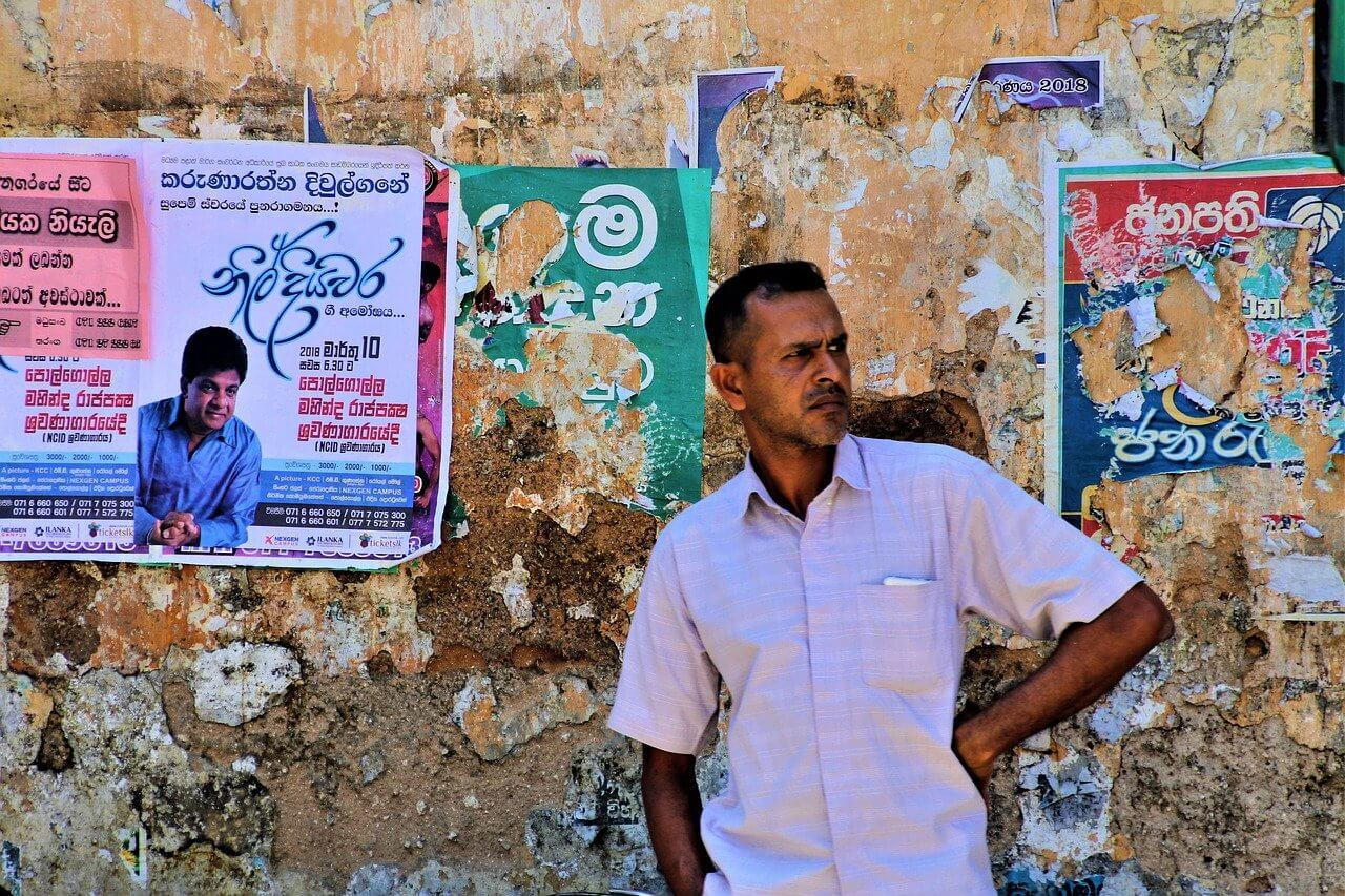 A Sri Lankan man stands in a street in front of Sinhalese posters