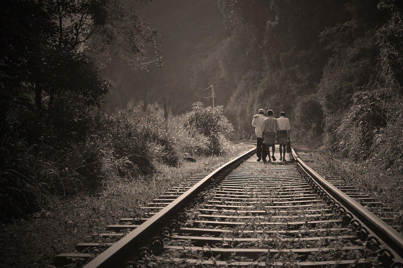 Three men in Sri Lanka walk the train tracks in the hill country