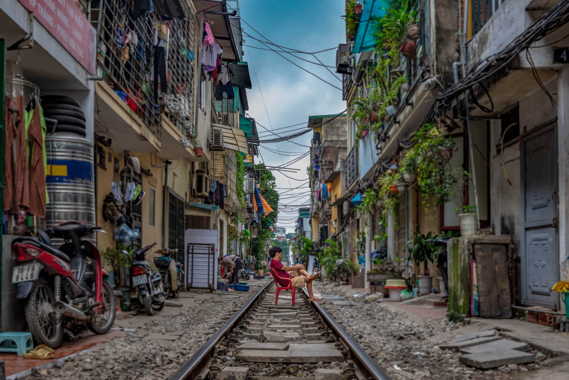 Boy sitting on the train tracks running through the Old Quarter in Hanoi