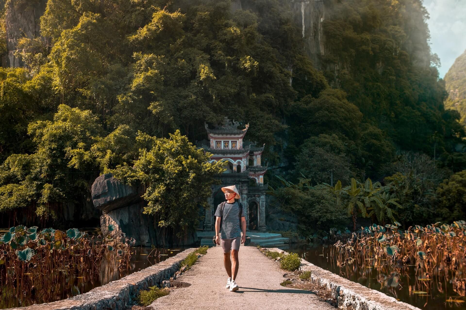 A backpacker in Vietnam walks on a bridge away from a cultural attraction