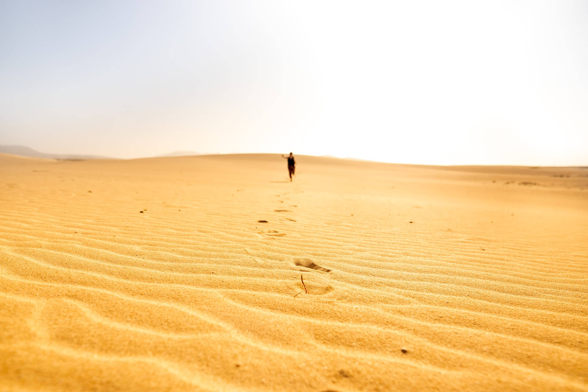 Woman running across sand dunes in the tropical Canary Islands