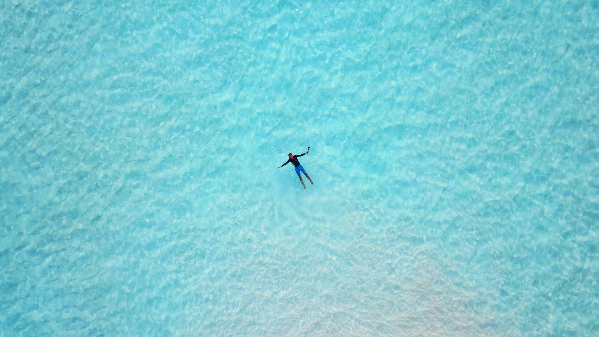 Man floating in the aquamarine waters of Raja Ampa - best tropical vacation spot in Indonesia
