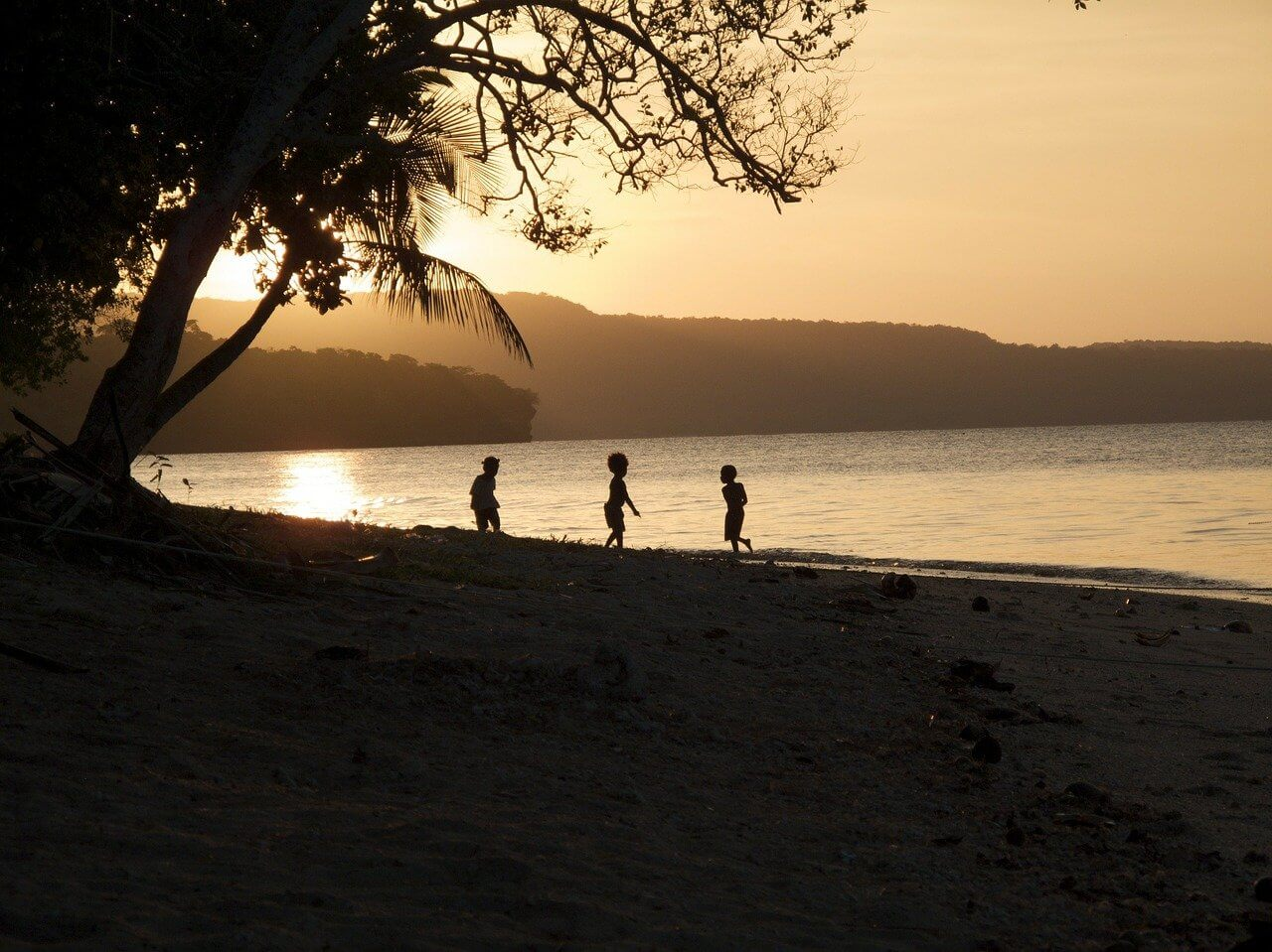 Young boys play on a sunset beach during a tropical holiday in Vanuatu