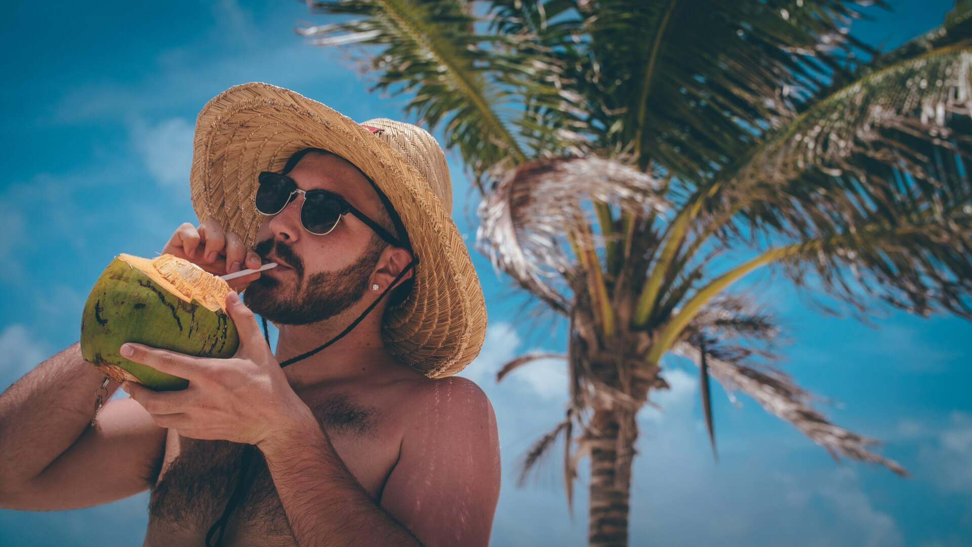 A man on vacation on a tropical island drinks from a coconut