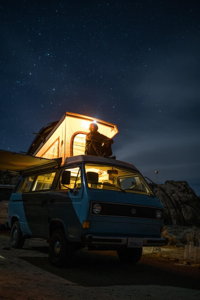 A man enjoys the stars from his van after planning an RV road trip