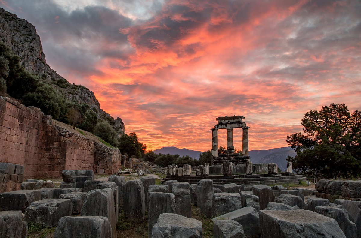Fiery sunset over the Temple of Athena in Delphi