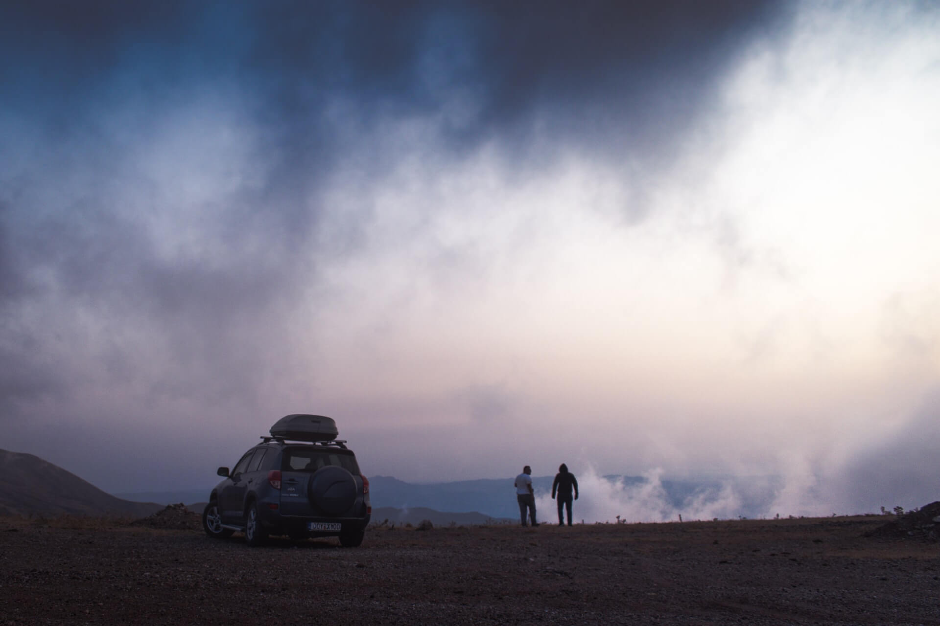 A travelling couple stand by their rental car on a misty morning in Greece