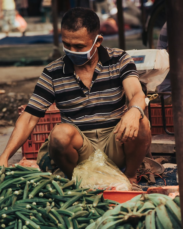 A man selling vegetables at a local street market in Nepal