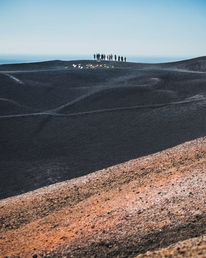 group of hikers climbing volcano