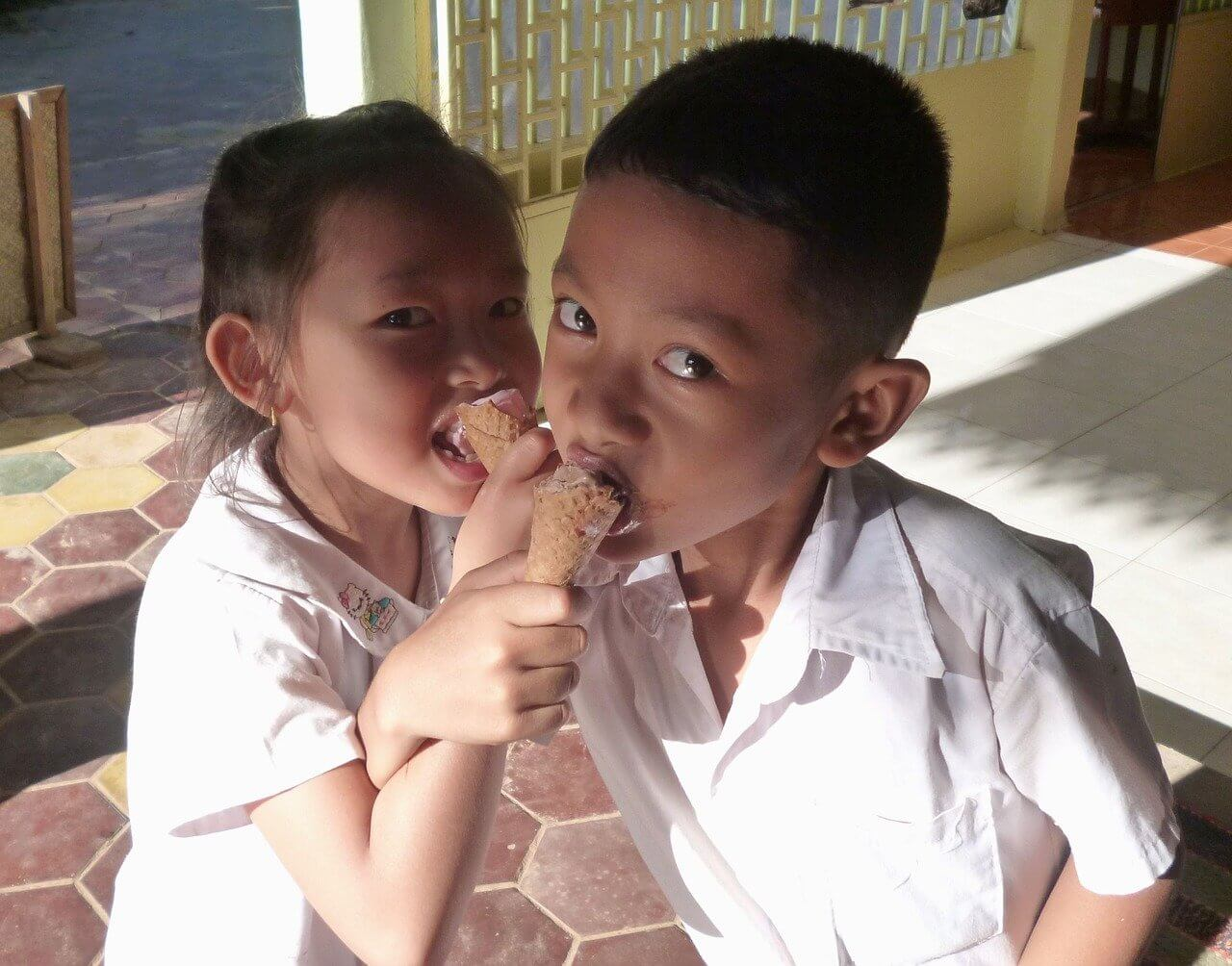 Two schoolkids in Cambodia eating ice-cream after their English lesson