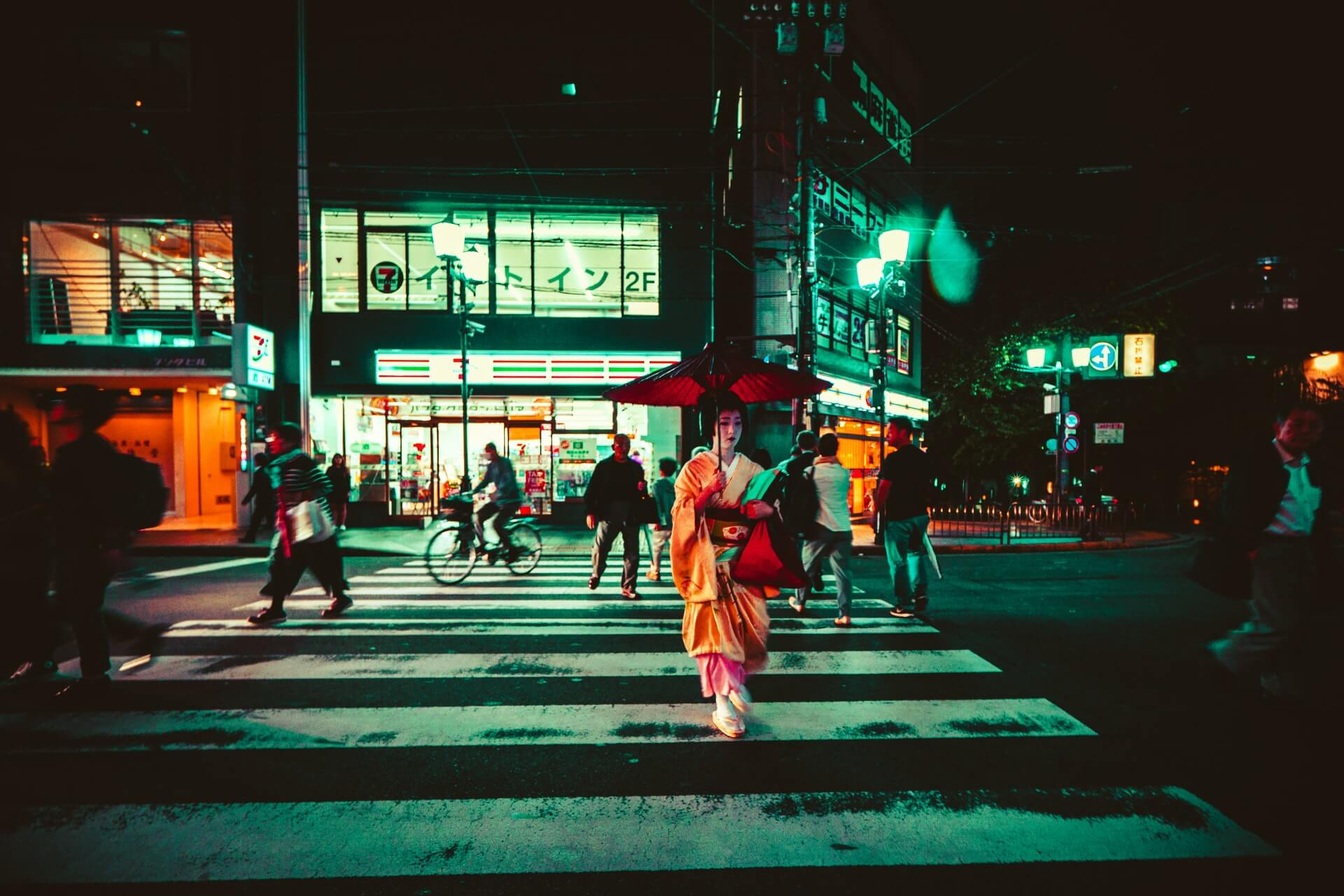 A geish in Kyoto crosses that street at night in front of a konbini